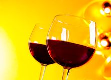 Two red wine glasses against golden lights background Stock Photos