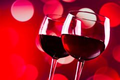 Two red wine glasses against red bokeh lights background Stock Photography