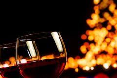 Two red wine glasses against tree of bokeh lights background Stock Photo