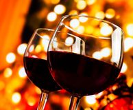 Two red wine glasses against tree of bokeh lights background Royalty Free Stock Image