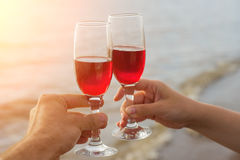 Two red wine glasses in couple hands silhouettes against sea sunset. Stock Photos