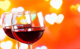 Two red wine glasses on hearts decoration bokeh lights background Stock Photography