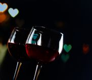 Two red wine glasses on hearts decoration bokeh lights background Stock Photo