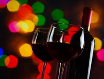 Two red wine glasses near bottle against colorful bokeh lights background. Festive and fun concept Royalty Free Stock Photo