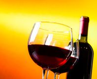 Two red wine glasses near the bottle against golden lights background Royalty Free Stock Photo