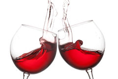 Two red wine glasses and splashing flow on white background. Celebration party concept. Macro view photo. Two red wine glasses and splashing flow on white Stock Image