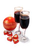 Two red wine glasses for Valentines day. Two glasses of red wine with chocolates hearts for Valentines day isolated on white background Royalty Free Stock Photo