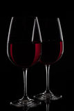 Two red wine glasses with wine on black background.  stock image