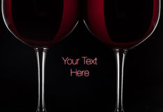 Two red wine glasses with wine on black background.  stock photography