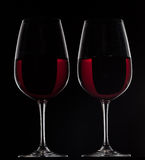 Two red wine glasses with wine on black background.  stock photos