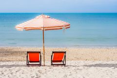 Two red wooden chairs and beach umbrella setting on white sand with seascape and blue sky in the background. Royalty Free Stock Photography
