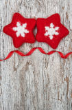 Two red woolen snowflake on the old wood background Stock Photography