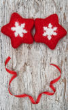 Two red woolen snowflake and ribbon on the old wood Stock Images
