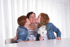 Two redhaired kids giving a present to their mother Stock Photos