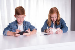 Two redhaired kids are playing with their smartphones Royalty Free Stock Image