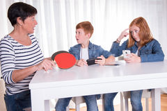 Two redhaired kids are playing with their smartphones- mother wa. Nts them to do sports Royalty Free Stock Photo