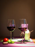 Two redwine glasses with tomato and basil. On table for couple Stock Images