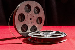Two reel of film  on a red table. Reel of film  on a red table with black background Stock Photos