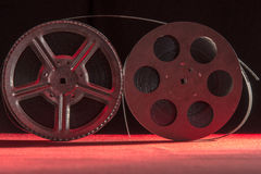 Two reel of film standing on a red table. Reel of film standing on a red table with black background Royalty Free Stock Image