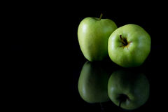 Two reflecting green apples on a black background Royalty Free Stock Image