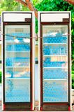 Two refrigerators full of water bottles under lock Stock Photo