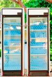 Two refrigerators full of water bottles under lock Stock Photo