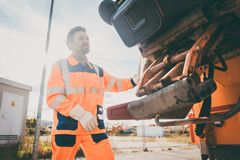 Two refuse collection workers loading garbage into waste truck. Emptying containers royalty free stock photo