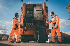 Two refuse collection workers loading garbage into waste truck. Emptying containers royalty free stock images