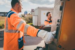Two refuse collection workers loading garbage into waste truck stock image