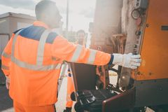 Two refuse collection workers loading garbage into waste truck stock photography