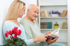 Two relatives looking through family album Royalty Free Stock Image