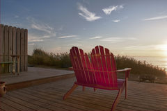 Two Red Adirondack Chairs. Red Adirondack chairs waiting to be used for a relaxing evening sunset on the Oregon coast Royalty Free Stock Images