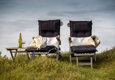 Two relaxation chairs and a glass of wine in the clear day light Royalty Free Stock Photos