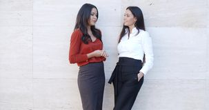 Two relaxed confident ladies standing chatting stock footage