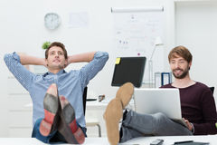 Two relaxed confident young business partners. Sure of their own success sitting with their feet up on the desk and complacent smiles Royalty Free Stock Photos