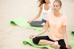 Two relaxed young girls sit in the lotus positions with closing eyes doing yoga on mats on sandy beach on a warm day royalty free stock photo