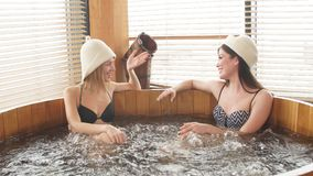 Two relaxing caucasian girl enjoying jacuzzi in hotel spa stock video