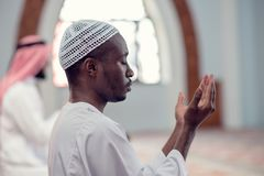 Two religious muslim man praying together inside the mosque Royalty Free Stock Image