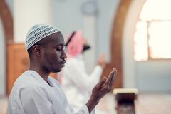 Two religious muslim man praying together inside the mosque Stock Photo