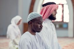 Two religious young people praying inside the mosque. islamic Stock Photos