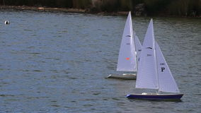 Two remote controlled sailing wooden yachts race in a pond. AUCKLAND, NZL - DEC 21 2014:Two remote controlled sailing wooden yachts race in a pond.The racing is stock video