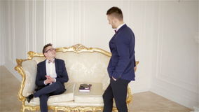 Two representative men in suits with bow ties communicate in a beautiful white room with elegant gold sofa. One man is sitting and second man is standing stock video footage