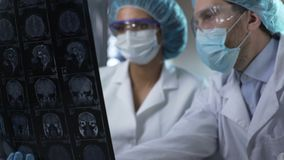 Two researchers studying human brain MRI, analyzing and discussing its condition. Stock footage stock video