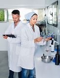 Two researchers in white coat checking wine acidity in laboratory Stock Image