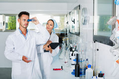 Two researchers in white coat checking wine acidity in laboratory Royalty Free Stock Photos