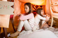 Two resentful sisters sitting on floor at bedroom back to back Stock Photo