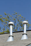 Two Residential Roof Exhaust Vents. A pair of residential roof exhaust vents on a asphalt shingled house top in the suburbs on clear blue sky day royalty free stock image