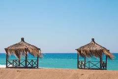 Two rest shacks on tropical beach on the shore of the ocean Royalty Free Stock Photos