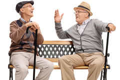 Two retired elderly people sitting on a bench and laughing. Isolated on white background Royalty Free Stock Photography