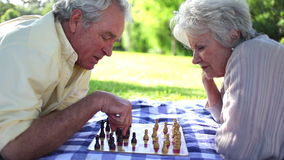 Two retired people playing chess. In a park stock footage